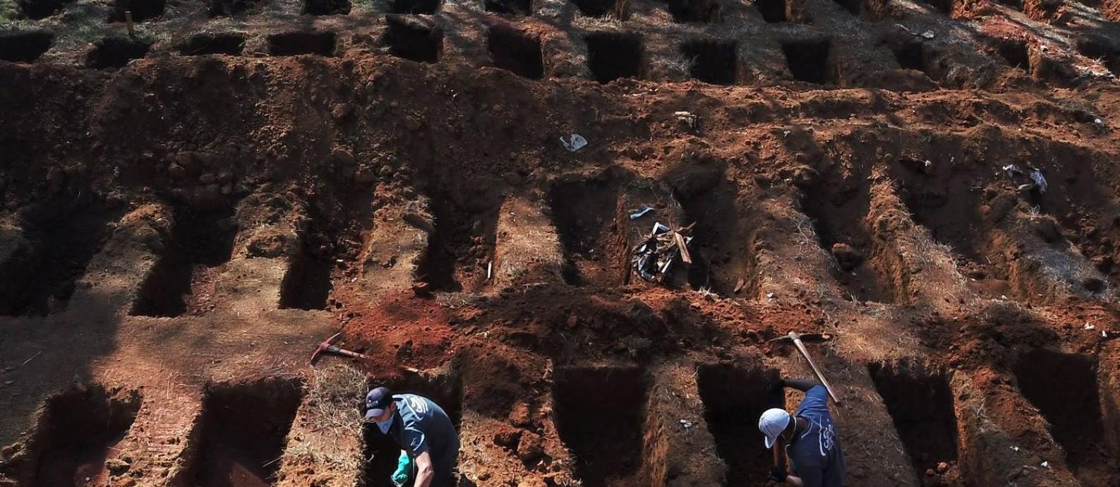 Coveiros abrem túmulos no cemitério VIla Formosa, em São Paulo (SP), na última quinta-feira; seis meses após primeira morte na cidade, local ainda expande número de covas para atender demanda Foto: AMANDA PEROBELLI / REUTERS