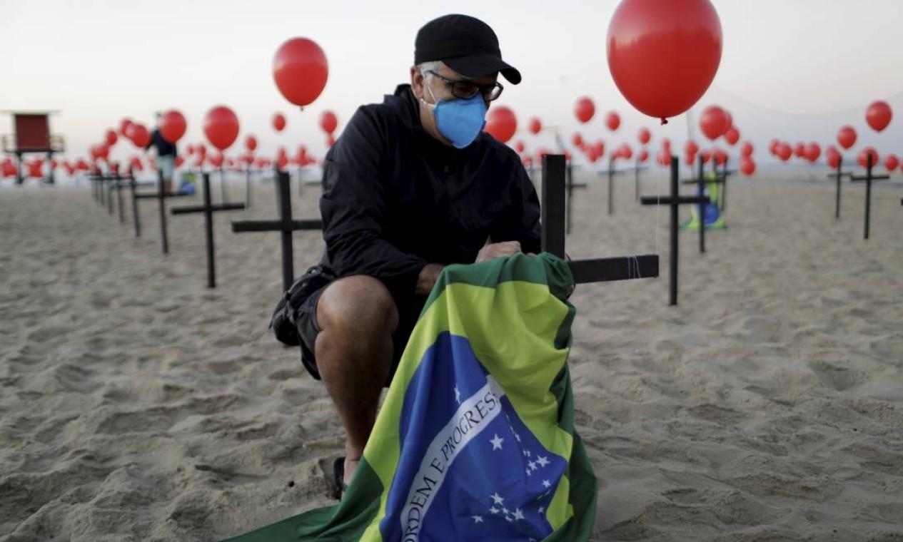 Manifestante coloca bandeira do Brasil em cruz que simboliza as vítimas da Covid-19 no país Foto: Gabriel de Paiva / Agência O Globo