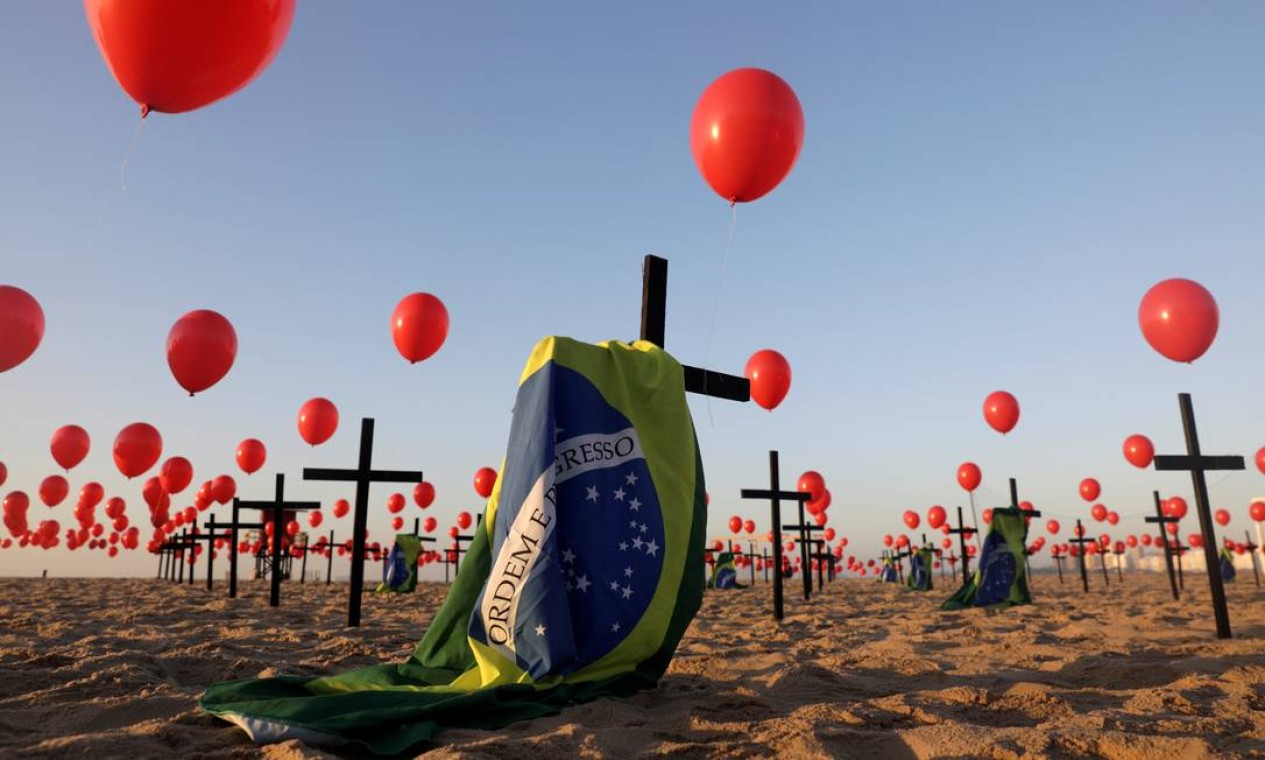 Cruzes foram fixadas na areia e balões vermelhos foram soltos para homenagear a trágica marca que o Brasil atingiu, cinco meses depois da primeira vítima registrada Foto: RICARDO MORAES / REUTERS