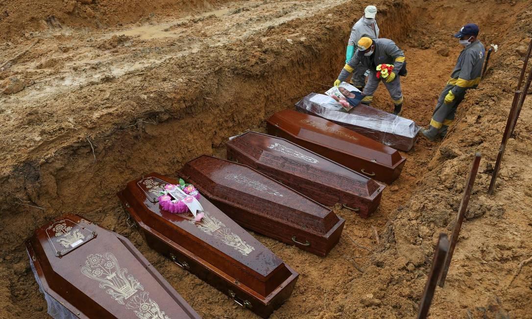 Coveiros com roupas de proteção contra a Covid-19 enterram vítimas da doença em vala comum no cemitério Nossa Senhora Aparecida, em Manaus (AM), cidade que sofreu colapso no sistema de saúde e funerário por conta do novo coronavírus Foto: MICHAEL DANTAS / AFP