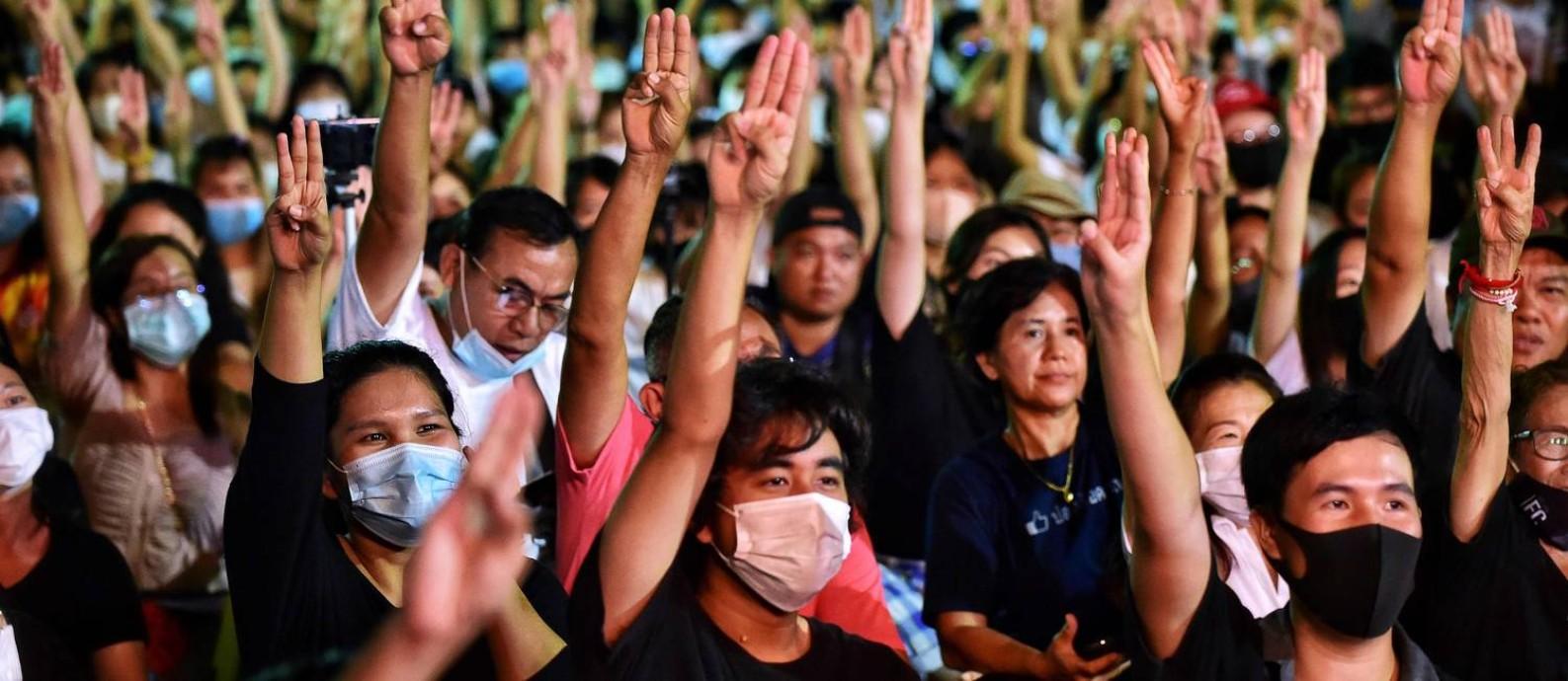 Manifestantes na Tailândia fazem o mesmo sinal com três dedos que é feito na saga Jogos Vorazes Foto: Lillian Suwanrumpha / AFP