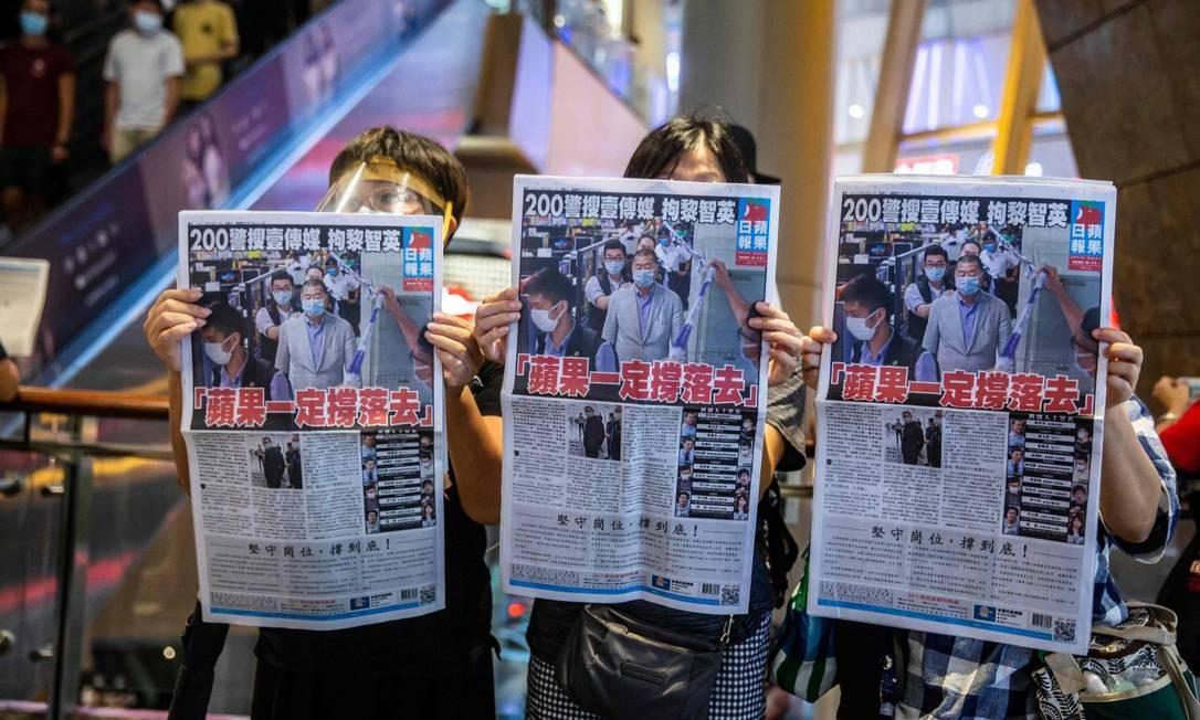 Ativistas pró-democracia carregam edições do Apple Daily, jornal de Jimmy Lai, magnata preso na segunda-feira Foto: ISAAC LAWRENCE / AFP