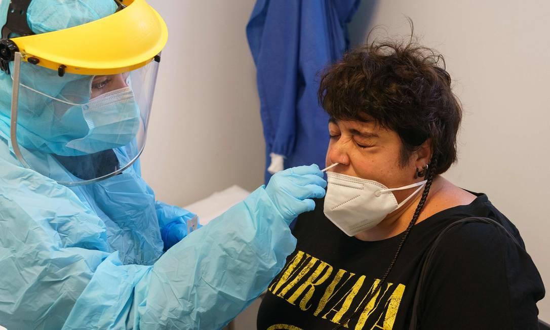 Profissional de saúde coleta amostras de uma mulher para detectar a COVID-19 no centro de saúde La Jota, em Saragoça. A Espanha registrou 19.405 novos casos de coronavírus na semana passada, mas o ministério da saúde diz que o país não está entrando em uma segunda onda da pandemia Foto: CESAR MANSO / AFP