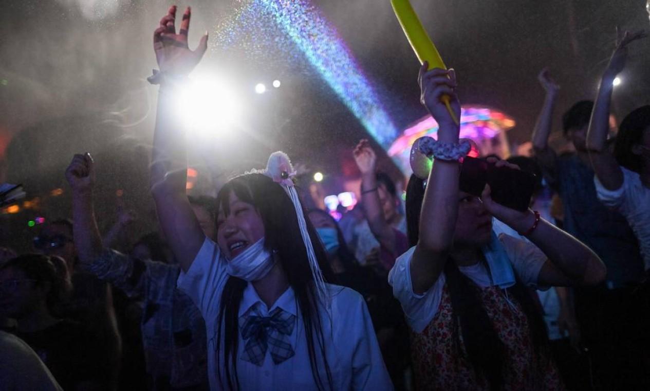 Pessoas sem máscara dançam em um festival de música em Wuhan. Muitos abaixaram a máscara, enquanto outros sequer carregam o acessório de proteção Foto: HECTOR RETAMAL / AFP - 04/08/2020