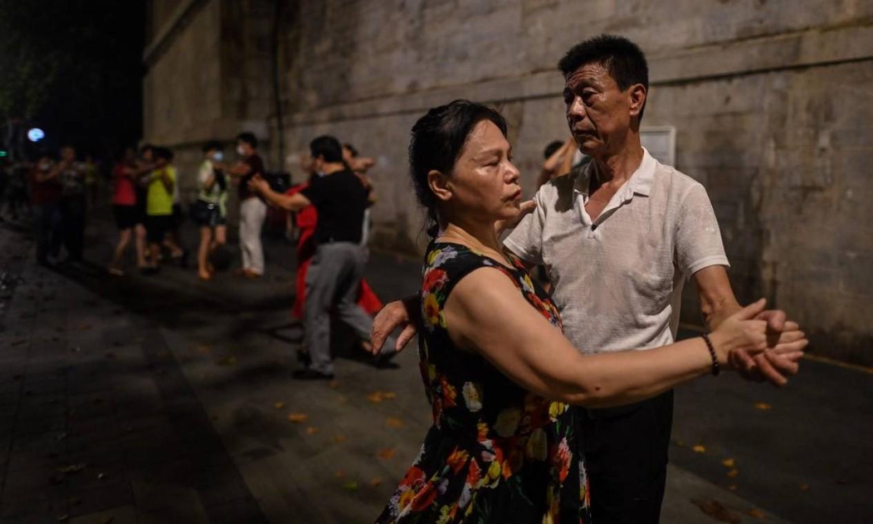 Casais dançando perto do rio Yangtze, em Wuhan, primeira cidade do planeta a entrar em quarentena Foto: HECTOR RETAMAL / AFP - 05/08/2020