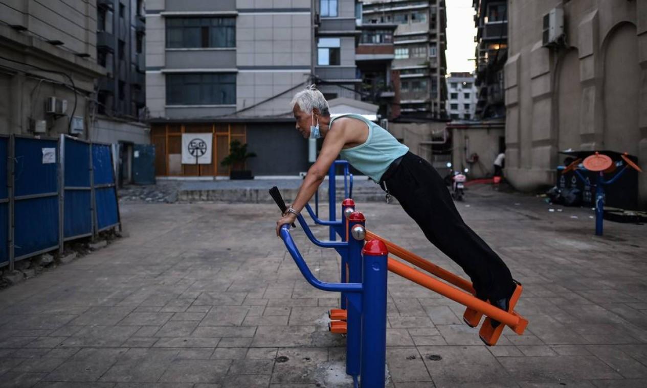 Homem se exercita em um equipamento público em um bairro de Wuhan. Cenas do atual cotidiano que em nada lembram as de multidões aterrorizadas que faziam fila nos hospitais da cidade nas primeiras semanas de bloqueio imposto no final de janeiro para conter a disseminação do coronavírus Foto: HECTOR RETAMAL / AFP - 03/08/2020