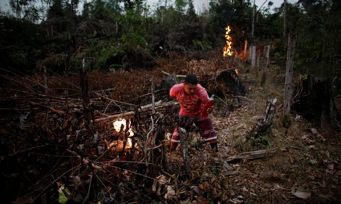 Voluntário acende uma fogueira para criar um aceiro para impedir o progresso de um incêndio iniciado por agricultores que limpam uma área da selva amazônica, em Apuí, no Amazonas Foto: UESLEI MARCELINO / REUTERS