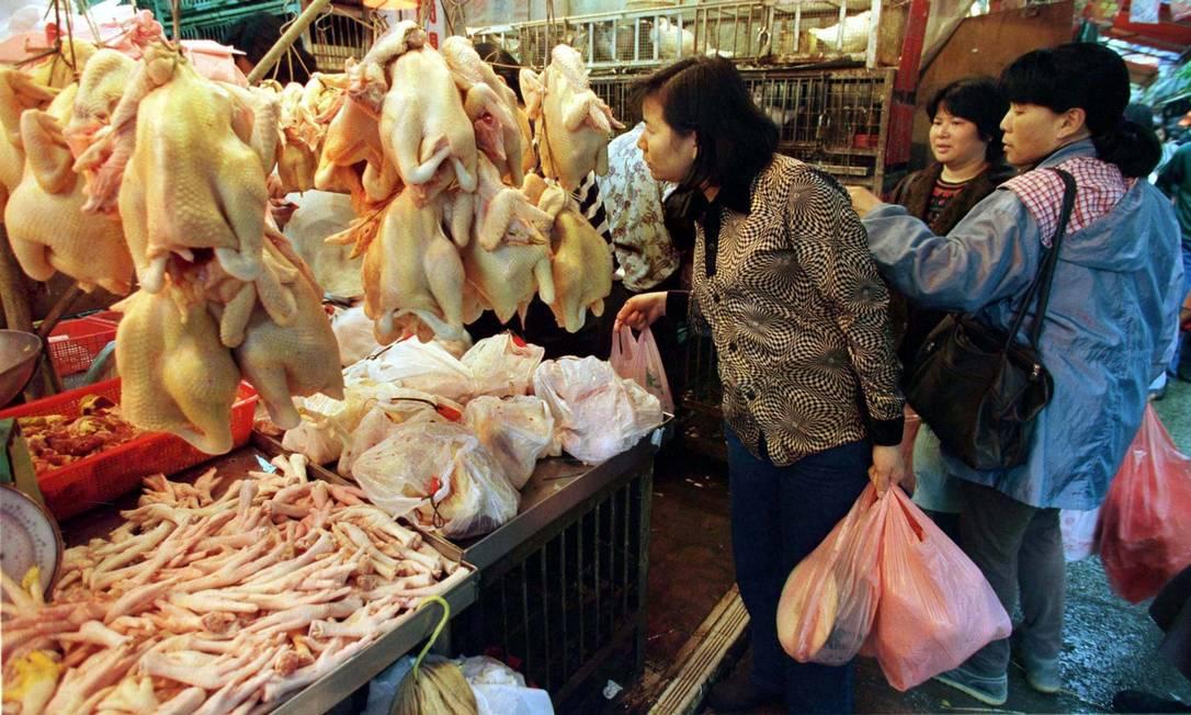 Mulheres observam frangos à venda em mercado de Hong Kong Foto: Bobby Yip / Reuters/22-12-2020