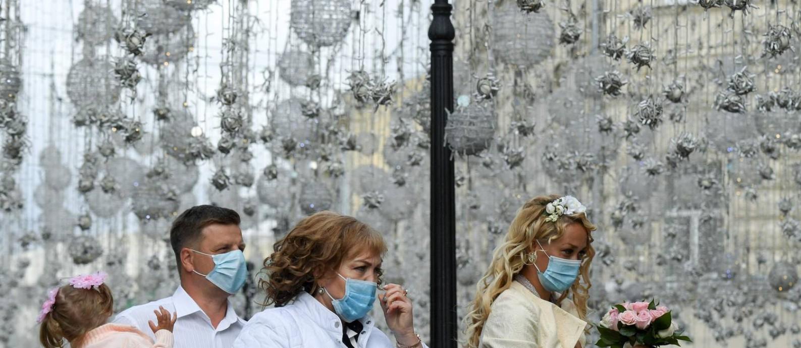 Pessoas caminham com máscaras no centro de Moscou, na Rússia; maioria dos médicos do país não confia na vacina registrada pelo governo, segundo pesquisa Foto: KIRILL KUDRYAVTSEV / AFP