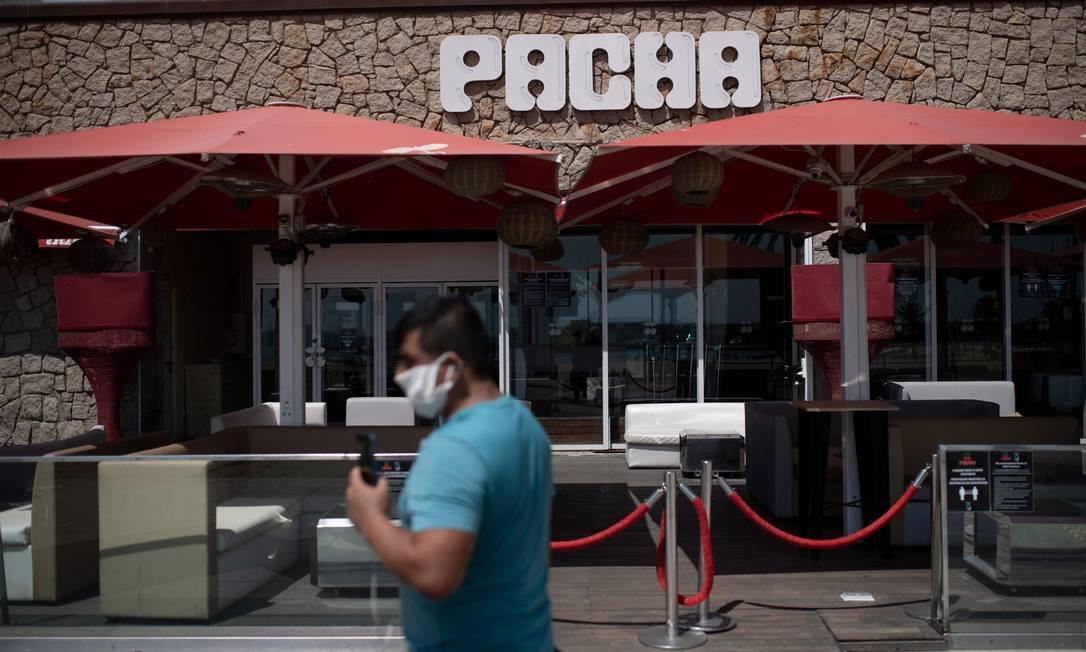 De máscara, homem caminha em frente a uma discoteca fechada em Barcelona Foto: Josep Lago / AFP