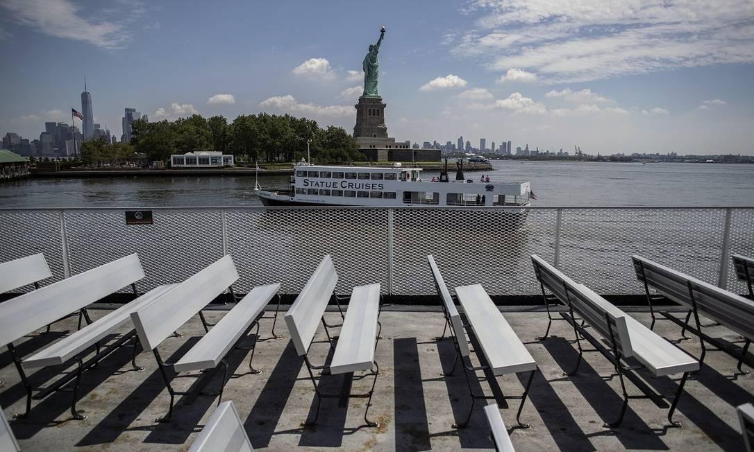 Um barco turístico passa em frente à Estátua da Liberdade, na Liberty Island, em Nova York Foto: Victor J. Blue / The New York Times