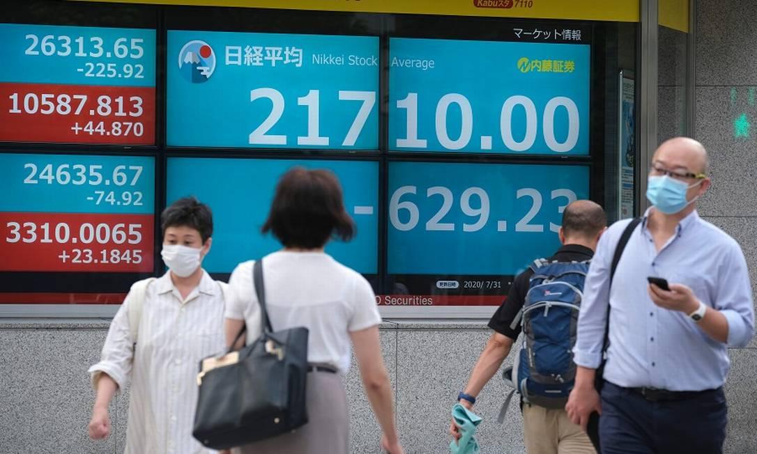 Pedestres passam por painéis da Bolsa de Tóquio: queda histórica no PIB com pandemia Foto: KAZUHIRO NOGI / AFP