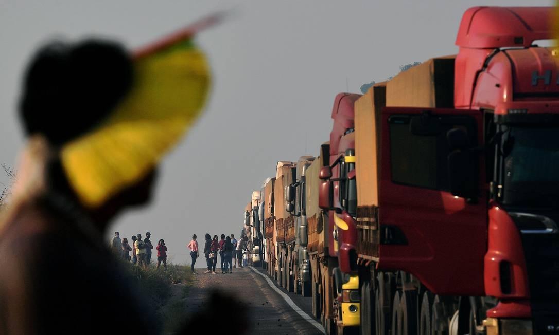 Indígena kayapó observa congestionamento de caminhões formado a partir do fechamento da rodovia BR-163, uma das principais vias de distribuição de cargas de grãos Foto: CARL DE SOUZA / AFP