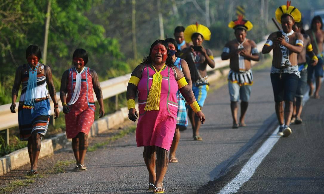 Indígenas da tribo Kayapó caminham pelo acostamento da rodovia BR-163. Um total de 618 indígenas morreram por conta da Covid-19 e 21 mil foram contaminados, de acordo com a Articulação de Povos Indígenas do Brasil (Apib) Foto: CARL DE SOUZA / AFP