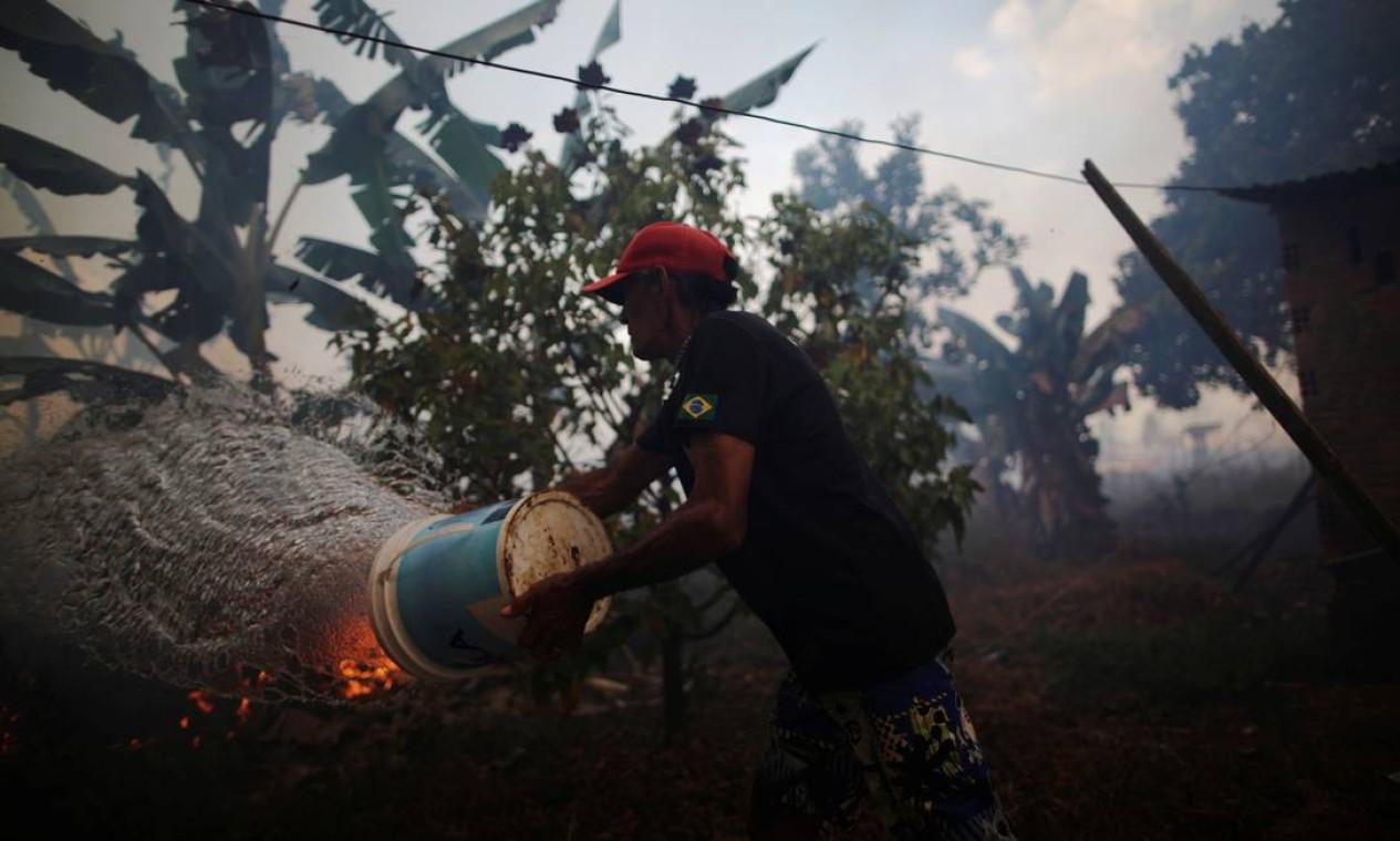 Rosalino de Oliveira joga água tentando proteger sua casa enquanto o fogo se aproxima em uma área da floresta amazônica, perto de Porto Velho, Rondônia Foto: UESLEI MARCELINO / REUTERS