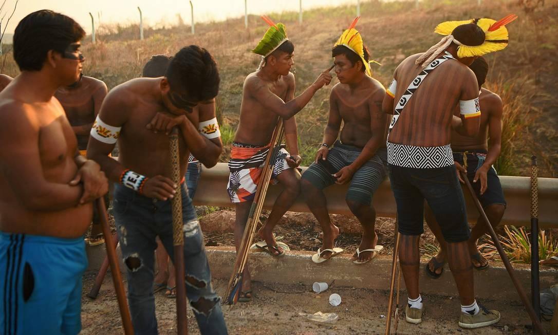 Indígena aplica pintura facial no acostamento da rodovia BR-163, enquanto mantém bloqueio Foto: CARL DE SOUZA / AFP