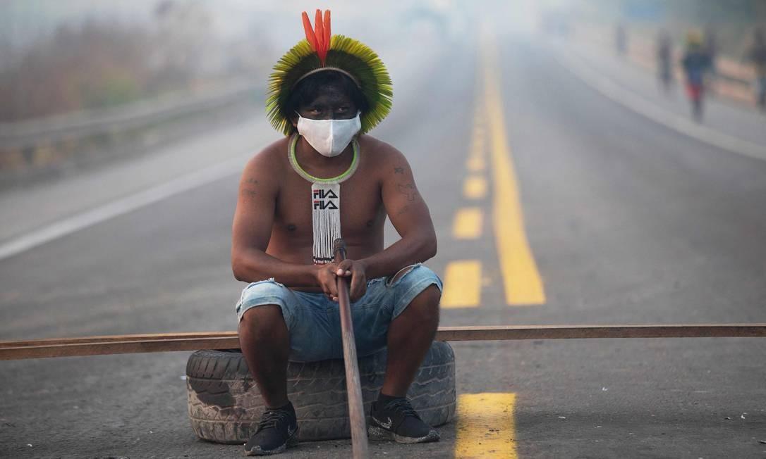 Membro da tribo Kayapó senta-se após bloquearem, pleo segundo dia, a rodovia BR-163, nesta terça-feira, nos arredores de Novo Progresso, no Pará Foto: JOAO LAET / AFP