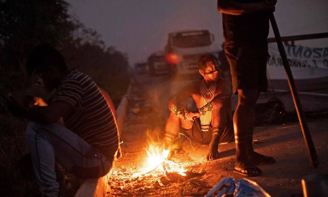 Indígenas descansam em volta de fogueira na madrugada desta terça-feira, mantendo o bloqueio na BR-163 Foto: JOAO LAET / AFP