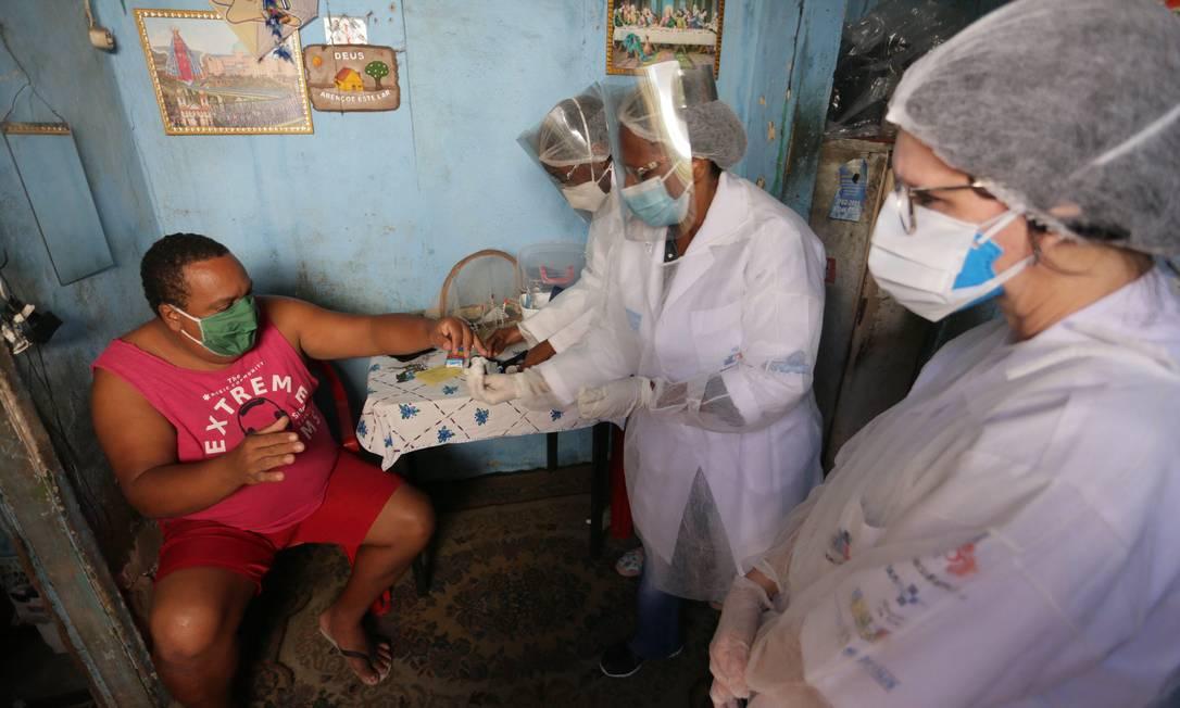 Agentes de saúde de Nilópolis, no Rio de Janeiro, fazem atendimento na casa de morador que teve Covid-19 Foto: Cléber Júnior / Agência O Globo
