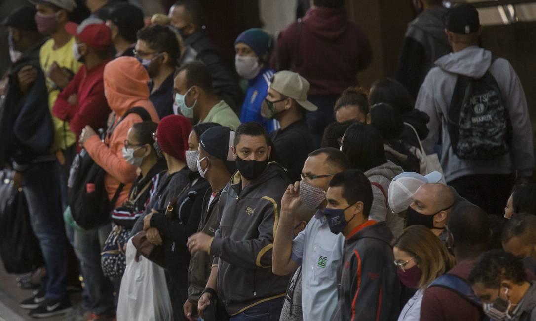 Em São Paulo, pessoas usam máscaras enquanto aguardam por chegada do trem para ir ao trabalho. Foto: Edilson Dantas / Agência O Globo