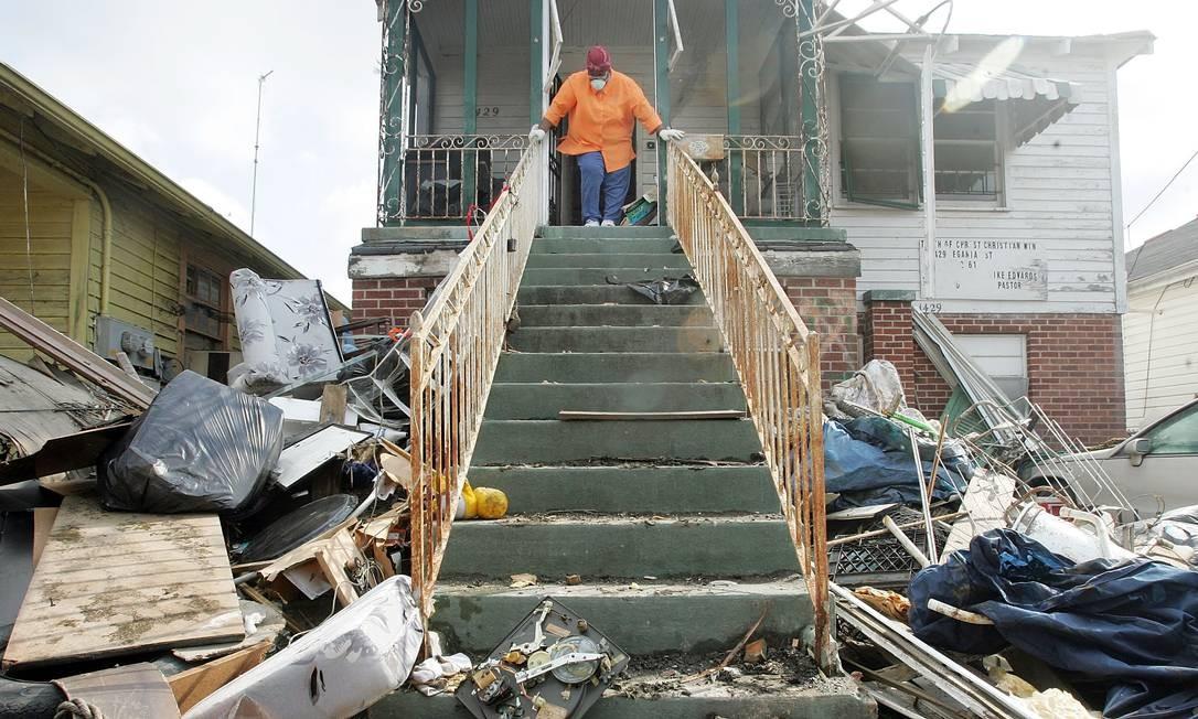 Moradora da Lower Ninth Ward vê os estragos na frente de sua casa, em Nova Orleans, após o furacão Katrina Foto: Mario Tama / Getty Images 21.11.2005