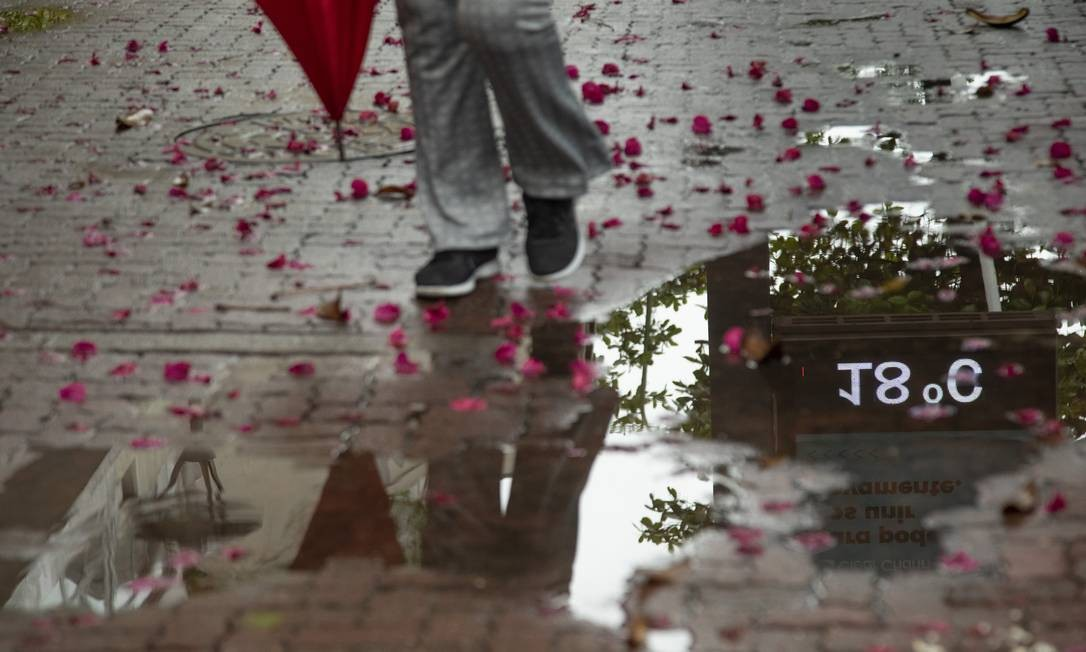 Cariocas que resolveram sair de casa tiraram casaco e guarda-chuva do armário; termômetro na Zona Sul marcou 18 graus à tarde: de acordo com a previsão, a máxima para este sábado Foto: Ana Branco / Agência O Globo