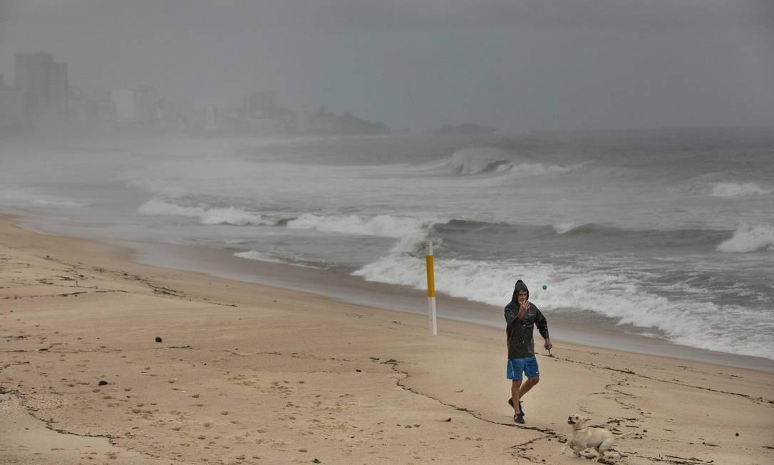 Mesmo com frio, chuva, cenário cinzento e mar agitado, teve quem se aventurasse tambén a passear com o cachorrinho na praia Foto: Ana Branco / Agência O Globo