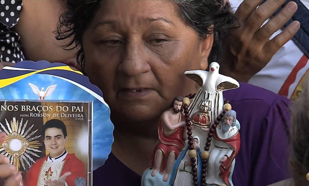 Fiel segura CD do padre Robson em evento na cidade de Recife, em 2011 Foto: Reprodução