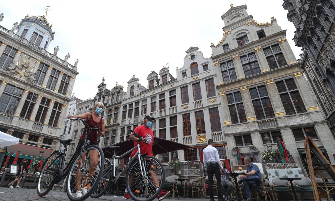 Pessoas caminham com máscaras contra o novo coronavírus em Bruxelas, capital da Bélgica Foto: YVES HERMAN / REUTERS