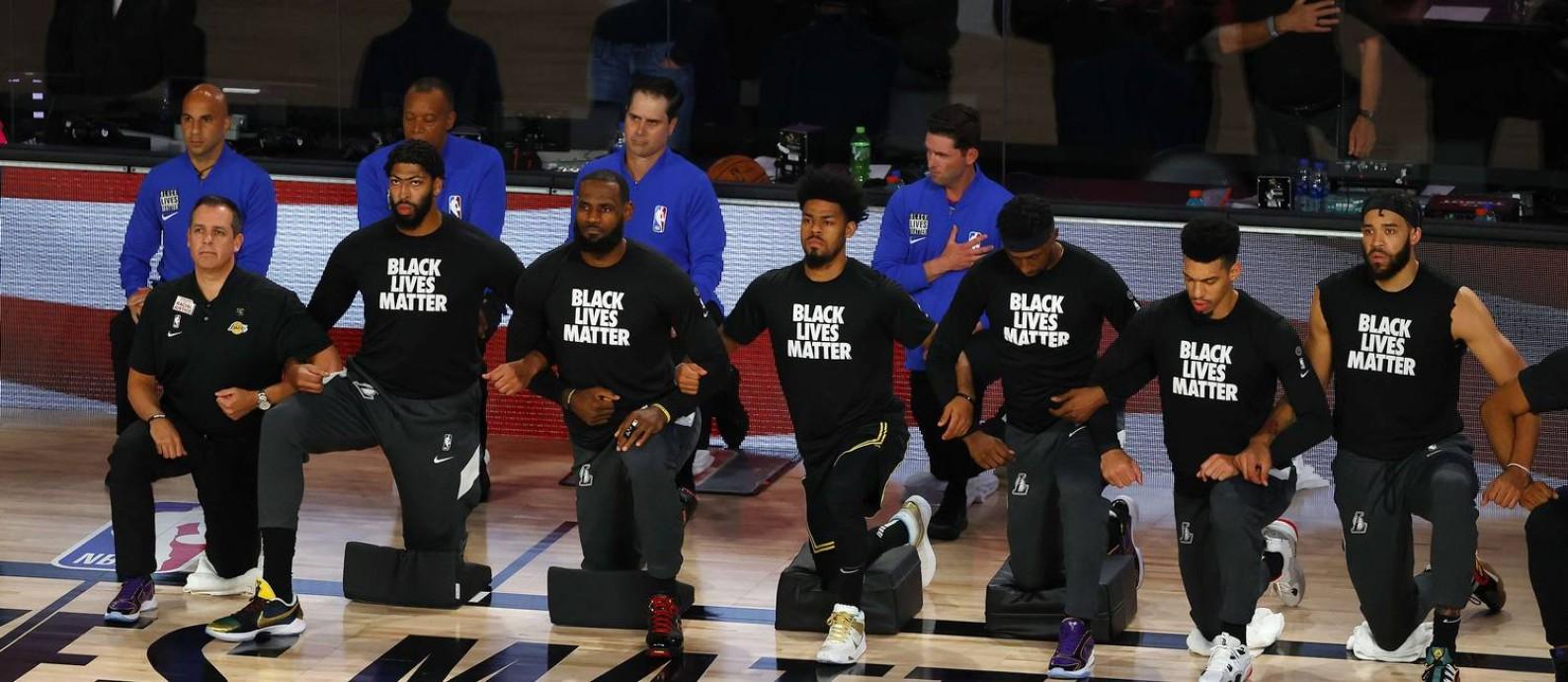 Jogadores do Los Angeles Lakers ajoelhados em protesto durante o hino americano Foto: Kevin C. Cox / AFP