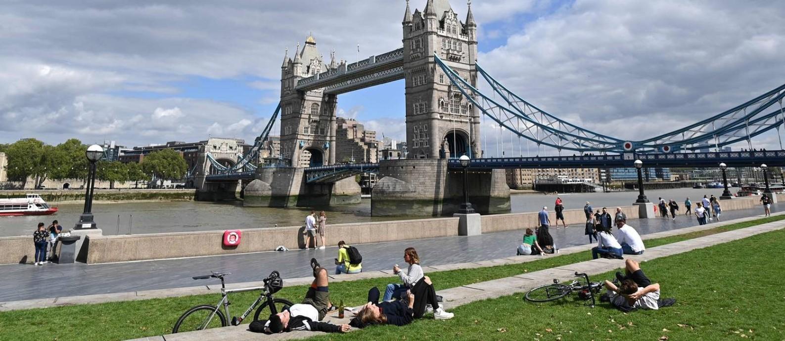 Pessoas aproveitam um dia de sol às margens do Rio Tâmisa, na altura da Tower Bridge, um dos cartões-postais de Londres Foto: JUSTIN TALLIS / AFP