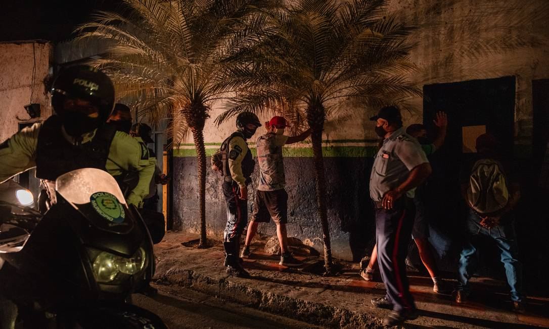 Policiais em Caracas revistam pessoas suspeitas de desrespeitarem a quarentena Foto: Adriana Loureiro Fernandez / New York Times