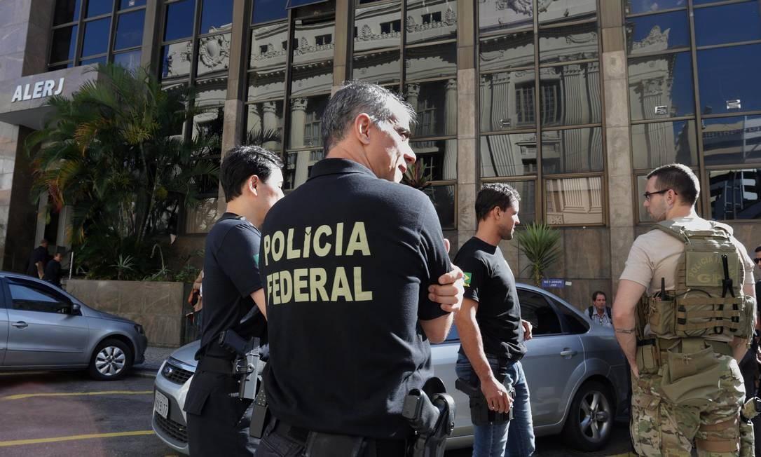 Agente da Polícia Federal com pistola no coldre durante operação na Alerj, em 2017: portaria permite manutenção de arma após aposentadoria Foto: Márcio Alves / Agência O Globo