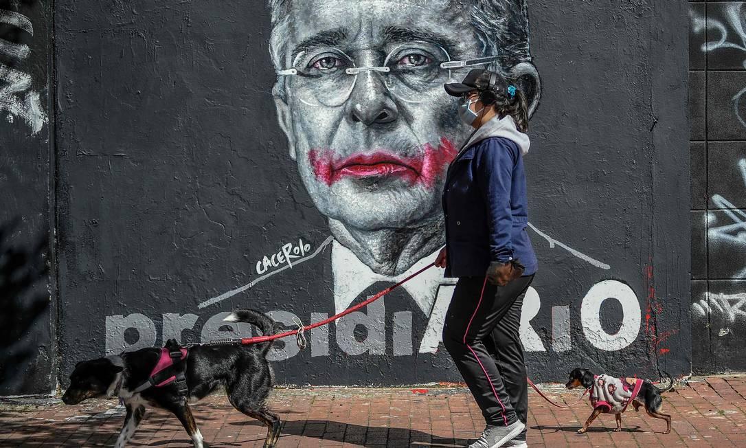 Mulher passa por cartaz de ex-presidente colombiano, Alvaro Uribe, em Bogotá: prisão domiciliar Foto: JUAN BARRETO / AFP