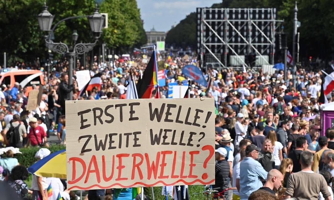 """Manifestantes carregam cartaz que diz """"Primeira onda! Segunda onda! Onda permanente?"""" em protesto em Berlim Foto: JOHN MACDOUGALL / AFP/29-08-2020"""