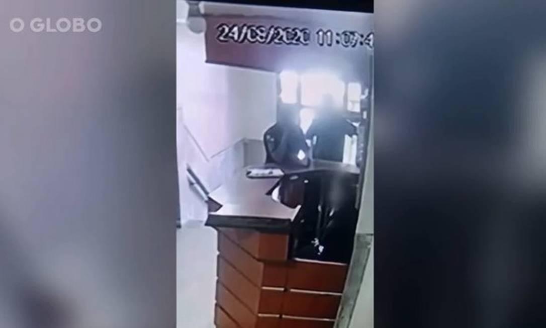 Câmeras de segurança registraram PM na portaria do prédio da vítima, acompanhado por outro agente Foto: Reprodução
