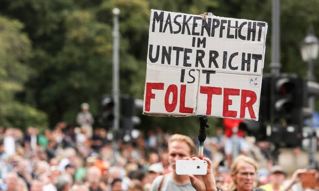 Cartaz mostra tônica do protesto: 'Máscara obrigatória na aula é tortura' Foto: Adam Berry / AFP