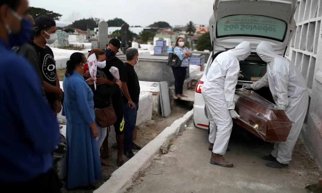 Caixão de vítima da Covid-19 é carregado por coveiros portando roupas de proteção contra o novo coronavírus em cemitério de Nova Iguaçu (RJ), na Baixada Fluminense, no último dia 20 Foto: Pilar Olivares / REUTERS