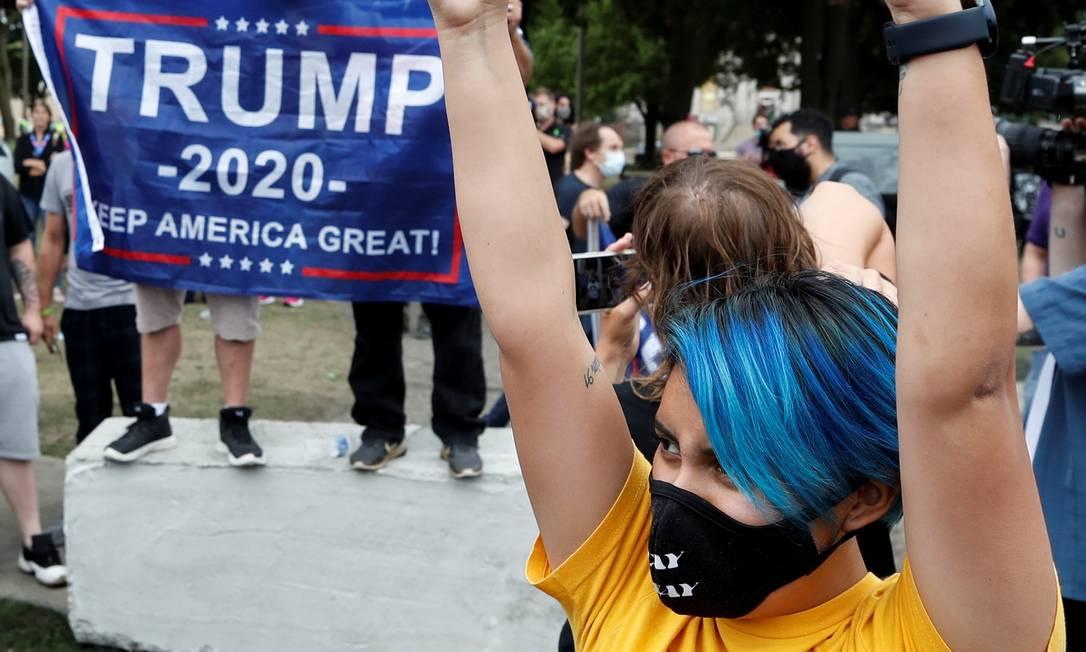 Um manifestante segura uma placa em frente aos apoiadores do presidente Trump no Civic Center Park Foto: KAMIL KRZACZYNSKI / REUTERS