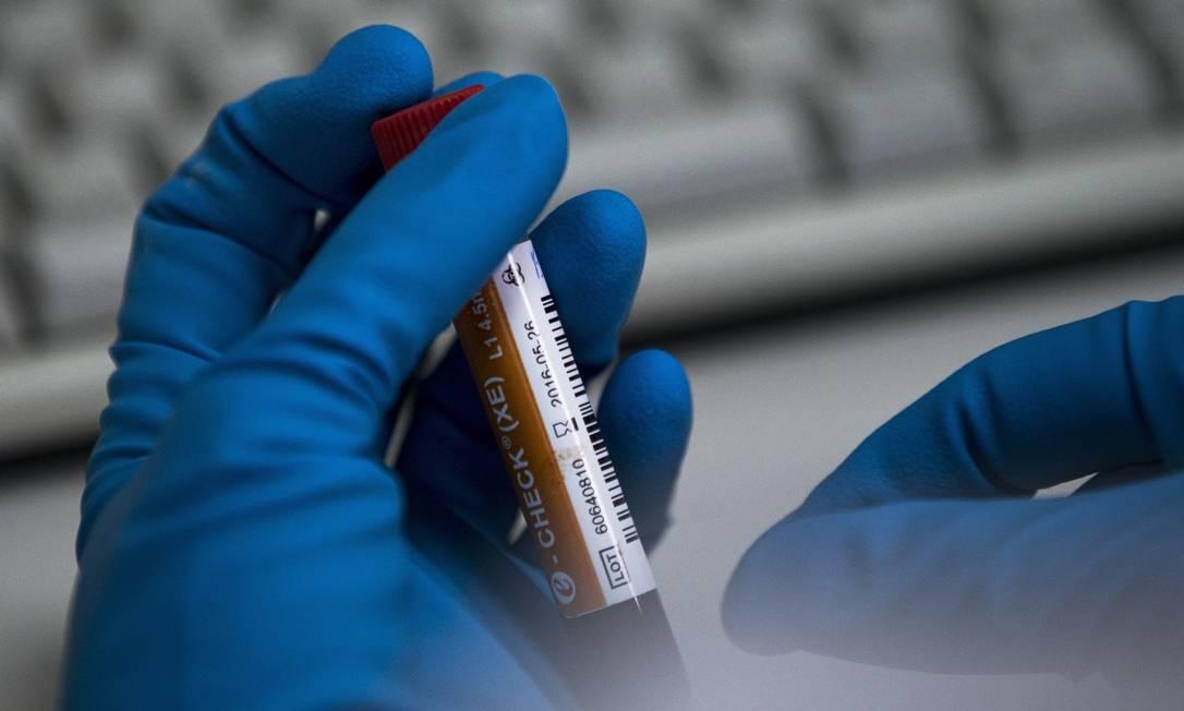 Funcionário de laboratório segura um frasco com teste de esteróides Foto: Alexander Zemlianichenko / AFP