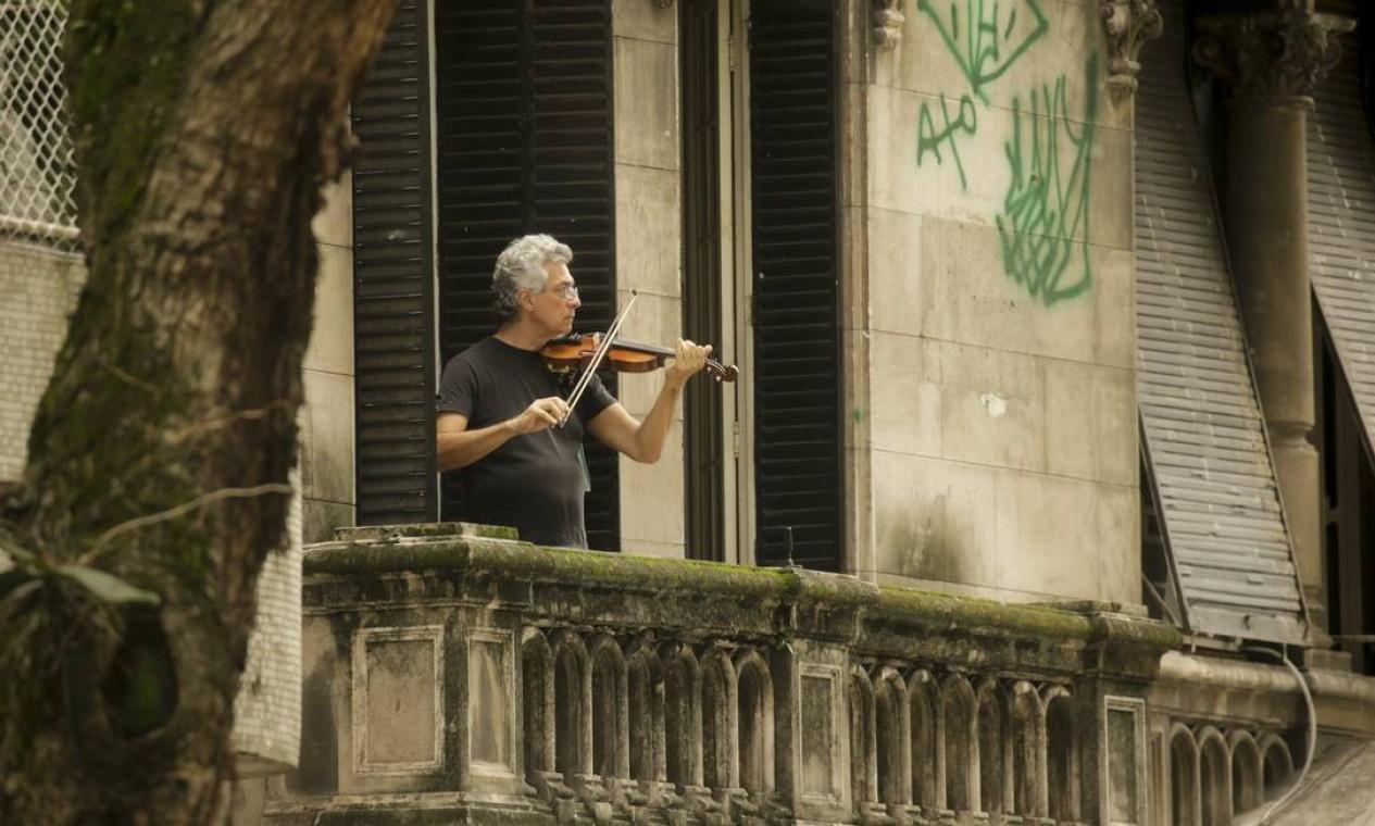 Música que vem das janelas. No auge do isolamento social, homem toca violino na sacada de seu apartamento na Avenida Oswaldo Cruz, no Flamengo, Zona Sul do Rio Foto: Gabriel de Paiva / Agência O Globo - 09/04/2020