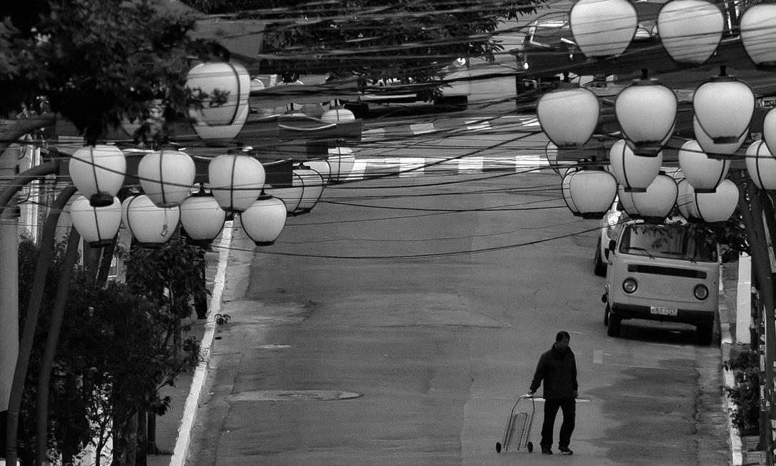 Homem caminha com carrinho de feira na Rua Galvão Bueno, Liberdade, quando o governador de São Paulo, João Doria, comemorava, em abril, a adesão de 59% da população às medidas de isolamento social. A meta de 70% nunca foi atingida Foto: Edilson Dantas / Agência O Globo