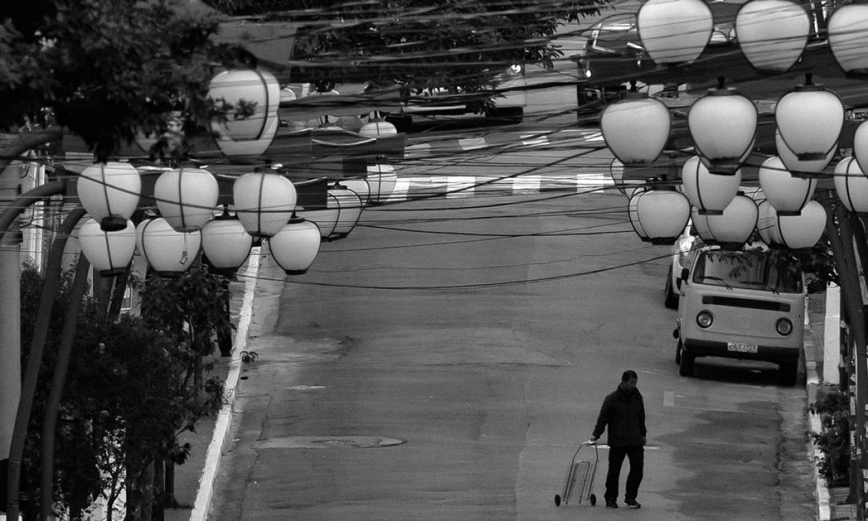 Homem caminha com carrinho de feira na Rua Galvão Bueno, Liberdade, quando o governador de São Paulo, João Doria, comemorava, em abril, a adesão de 59% da população às medidas de isolamento social. A meta de 70% nunca foi atingida Foto: Edilson Dantas / Agência O Globo - 15/04/2020