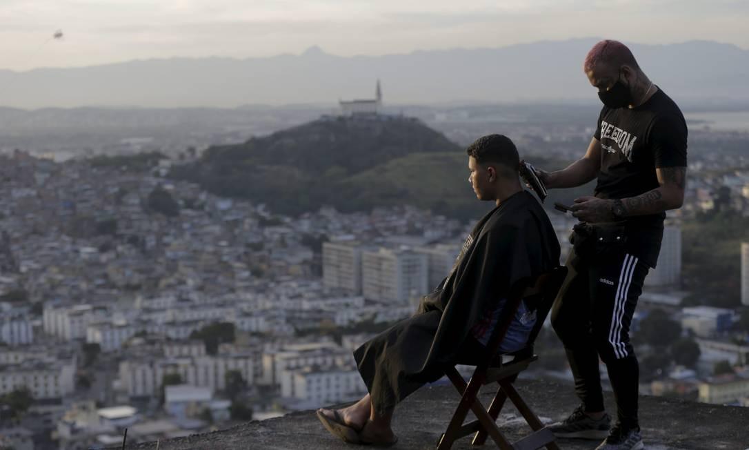 Barbeiro delivery do Complexo do Alemão, Renan Estate atende clientes na laje para tentar driblar a crise Foto: Domingos Peixoto / Agência O Globo