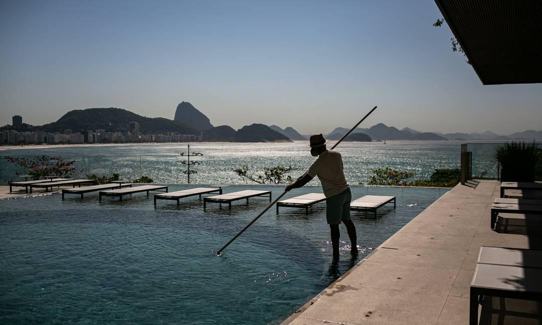 Funcionário do Fairmont, na Avenida Atlântica, em Copacabana, prepara a piscina para a chegada dos hóspedes: taxa média de ocupação de 50% é vista com bons olhos pelos hotéis Foto: Hermes de Paula / Agência O Globo