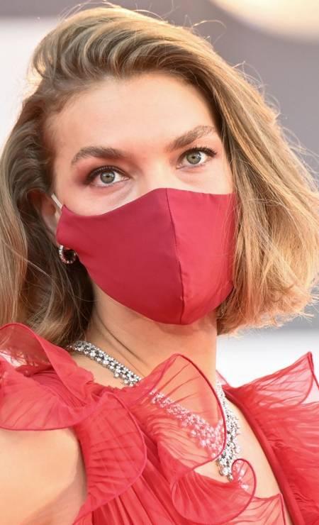 Máscara vermelha para combinar com o vestido no look de Arizona Muse Foto: ALBERTO PIZZOLI/AFP