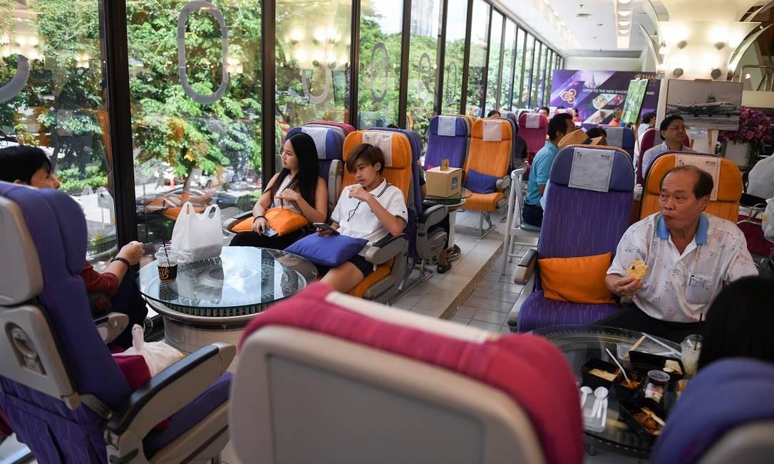 Clientes no restaurante pop-up da Thai Airways que emula o ambiente de um avião, em Bangcoc Foto: CHALINEE THIRASUPA / REUTERS