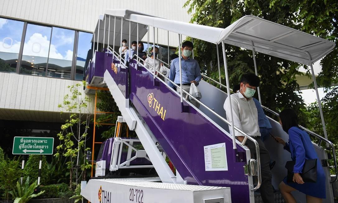 Uma escada, usada para embarques em plena pista, serve de acesso para os clientes Foto: CHALINEE THIRASUPA / REUTERS