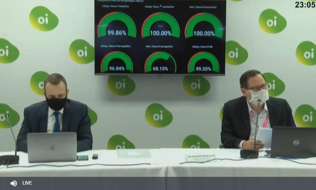 Rodrigo Abreu, presidente da Oi (esquerda), na mesa com Arnoldo Wald Filho, que presidiu a assembleia de credores. Atrás, o placar da votação virtual Foto: Reprodução