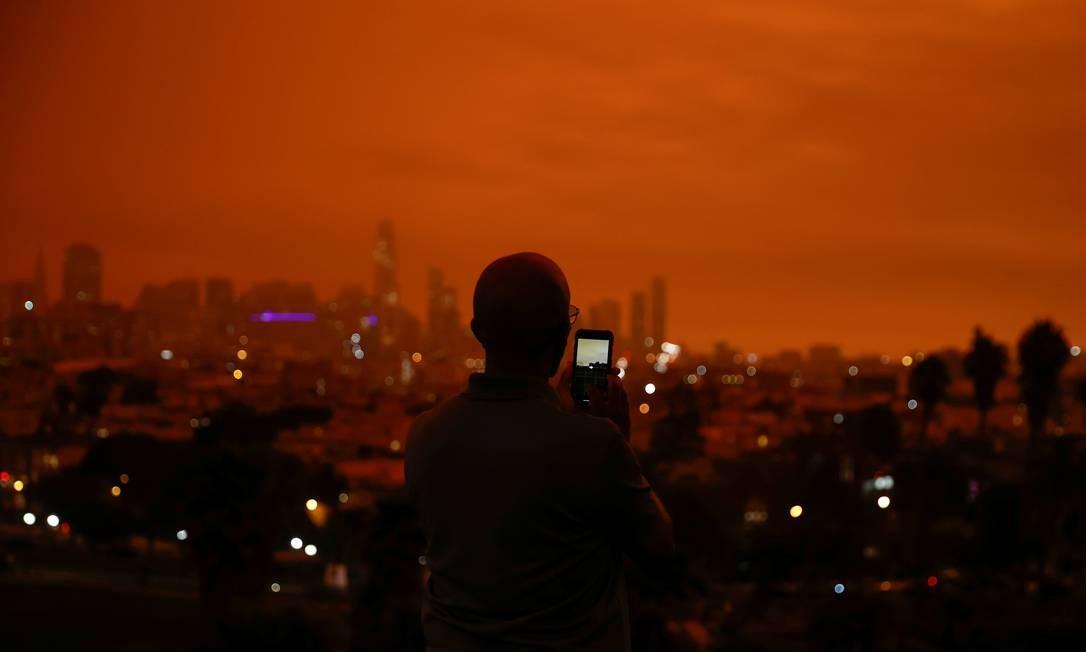 Homem fotografa o céu laranja no centro de São Francisco, em Dolores Park, Califórnia, EUA Foto: STEPHEN LAM / REUTERS